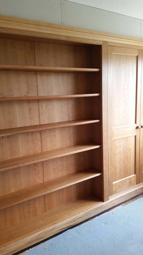 Traditional fitted wardrobes in Woodford Green, Essex. Wardrobes in alcoves, fixed shelves spanning across chimney breast. All in Cherrywood, finished with hardwax oil.