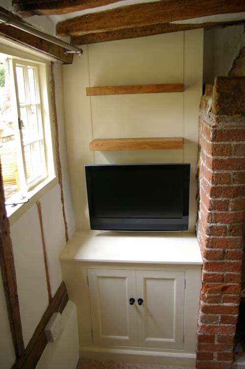 Alcove unit in cottage near Clavering, Essex. False back to conceal pipework and provide conduit for tv wiring. Led lights under shelves.