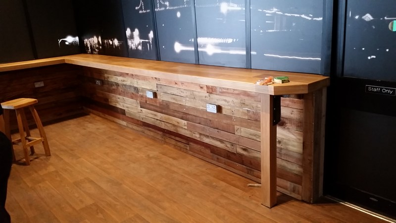 Walls in Essex restaurant, finished with used pallet planks. Continuous oak bar.