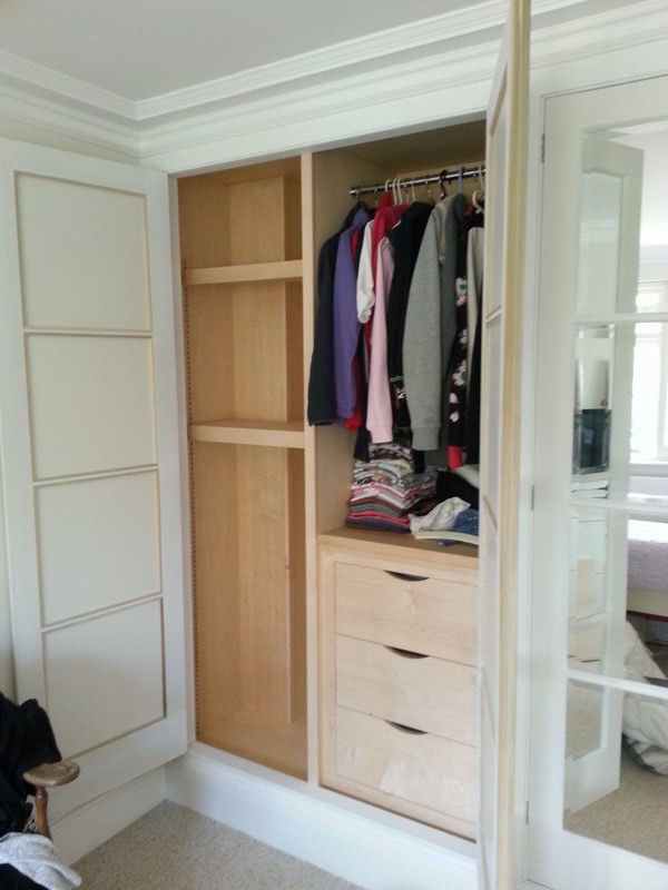 Bespoke wardrobes in separate rooms of house in North London. Traditional handmade doors, with bevel-edged mirrors as panels. Internals in combination of solid Maple & Maple veneered mdf. Elliptical drawer handles. The rooms' bespoke cornice mounted directly onto wardrobe frames